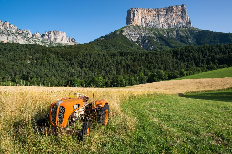 Vieux tracteur orange dans un champ devant le Mont Aiguille