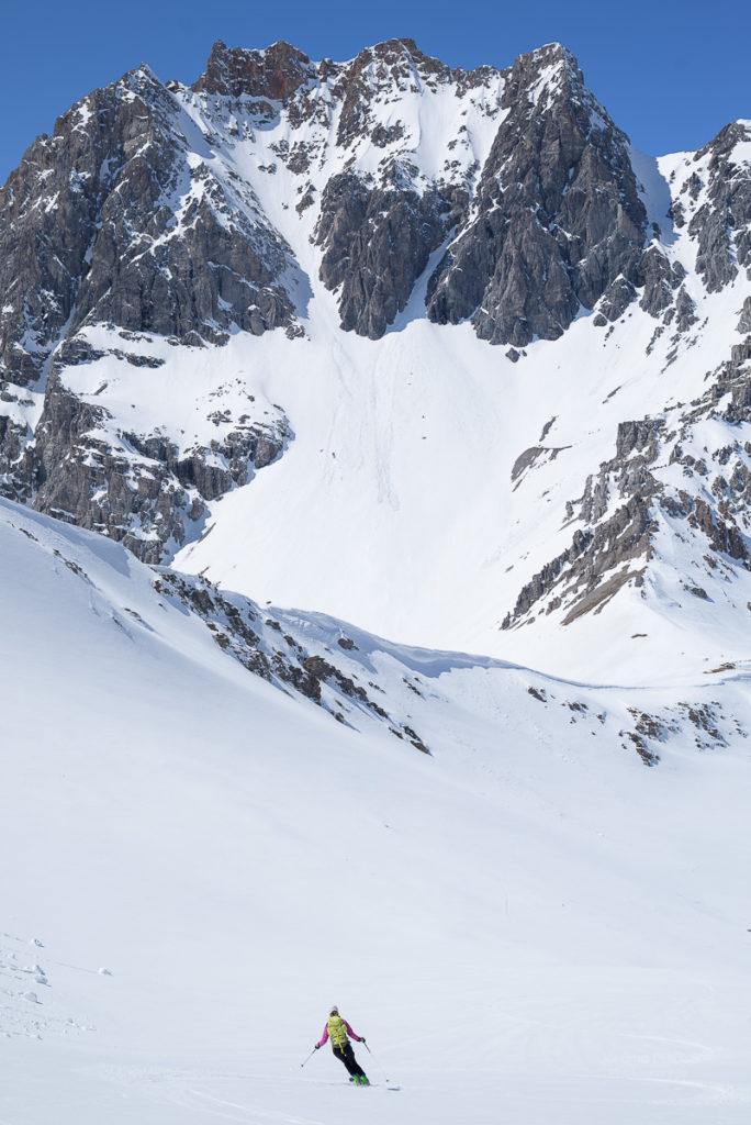 Skieuse faisant des virages seule devant une montagne. Massif des Cerces.