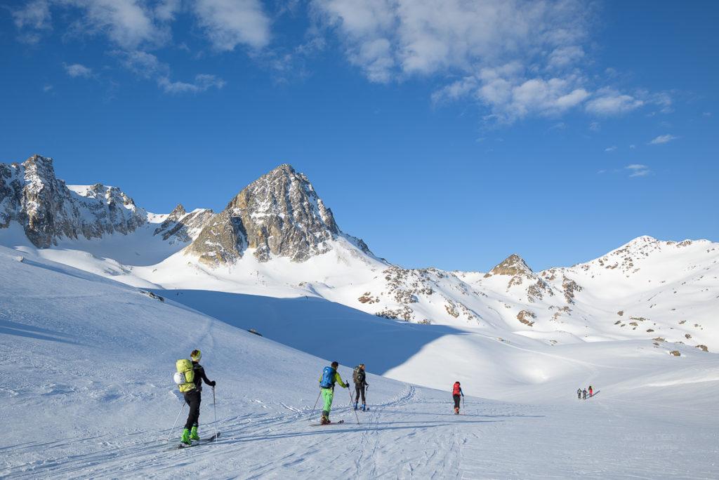 Skieurs au col du Cheval Blanc en route vers le Mont-Thabor. Ciel bleu et nuages. Massif des Cerces.