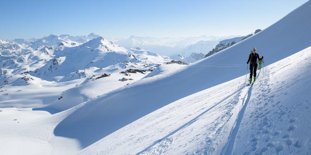 Randonneuse à skis au soleil sous le ciel bleu devant un magnifique panorama. Massif des Cerces