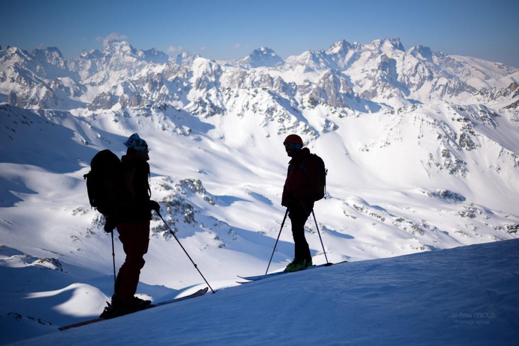 Deux skieurs en ombre chinoise devant les Ecrins au passage du Pic du Thabor. Massif des Cerces.
