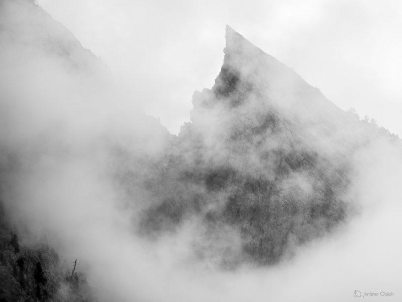 Aiguille des Deux Aigles dans la brume et les nuages dans les Aiguilles de Chamonix, massif du Mont-Blanc. Cette aiguille rocheuse de granit se situe en haute-montagne et est pointue et effilee. Le noir et blanc lui confere une atmosphere et ambiance mysterieuse.