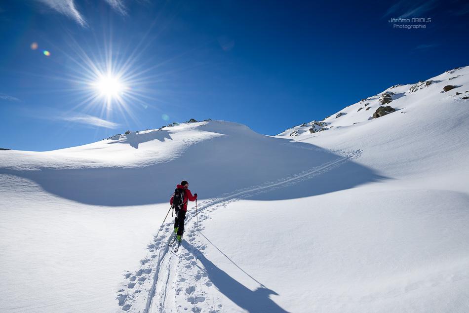 Skieur de randonnee en montee sous le soleil et ciel bleu. Grand-Mont. Massif du Beaufortin.