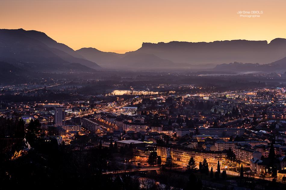 La ville d'Albertville et la combe de Savoie au crépuscule, avec les sommets de Chartreuse et la Dent de Crolles en arriere-plan.