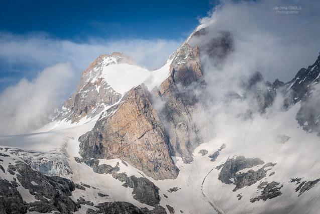 Le versant ouest des Tetes du Replat (3429m), entoure de nuages. Parc National des Ecrins.