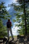 Personnage dans la forêt sur le sentier de la Jonction à un point de vue sur le glacier des Bossons.