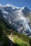 Personnage sur un sentier devant un glacier. Glacier du Taconnaz. Dôme du Gouter et Aiguille du Gouter en arrière plan.