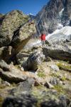 Personnage avec veste rouge et blocs de granit à la Jonction. Massif du Mont-Blanc.
