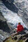 Personnage avec veste rouge assis sur un bloc de rocher devant un glacier à la Jonction. Massif du Mont-Blanc.