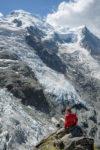 Personnage avec veste rouge assis sur un bloc de rocher devant un glacier et le Dome du Gouter à la Jonction. Massif du Mont-Blanc.