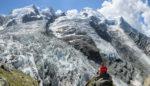Panorama avec personnage avec veste rouge assis sur un bloc de rocher devant un glacier et le Dome du Gouter à la Jonction. Massif du Mont-Blanc.
