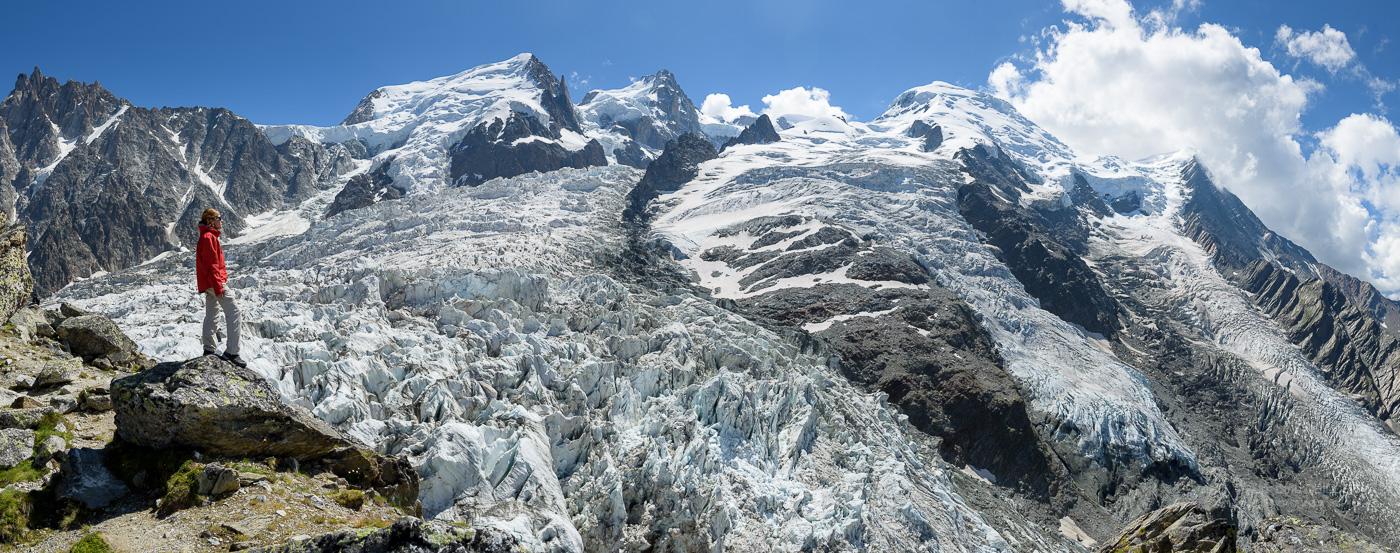 Panorama avec personnage avec veste rouge debout devant le glacier des Bossons à la Jonction. Massif du Mont-Blanc.