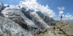 Panorama avec personnage avec veste rouge debout sur un bloc de rocher devant les glaciers et le Dôme du Goûter à la Jonction. Massif du Mont-Blanc.