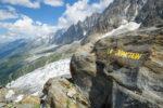 """Inscription """"la Jonction"""" peinte en jaune sur un rocher devant les Aiguilles de Chamonix. Massif du Mont-Blanc."""