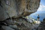 Randonneur devant le Gîte à Balmat à la Jonction. Bloc de granit sous lequel dormirent Jacques Balmat et Michel Gabriel Paccard lors de leur premières ascension du Mont-Blanc le 7 août 1786. Massif du Mont-Blanc.