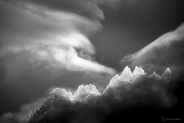Ciel d'orage en noir et blanc en montagne et lumière éclairant le sommet des aiguilles de Chamonix. Massif du Mont-Blanc.