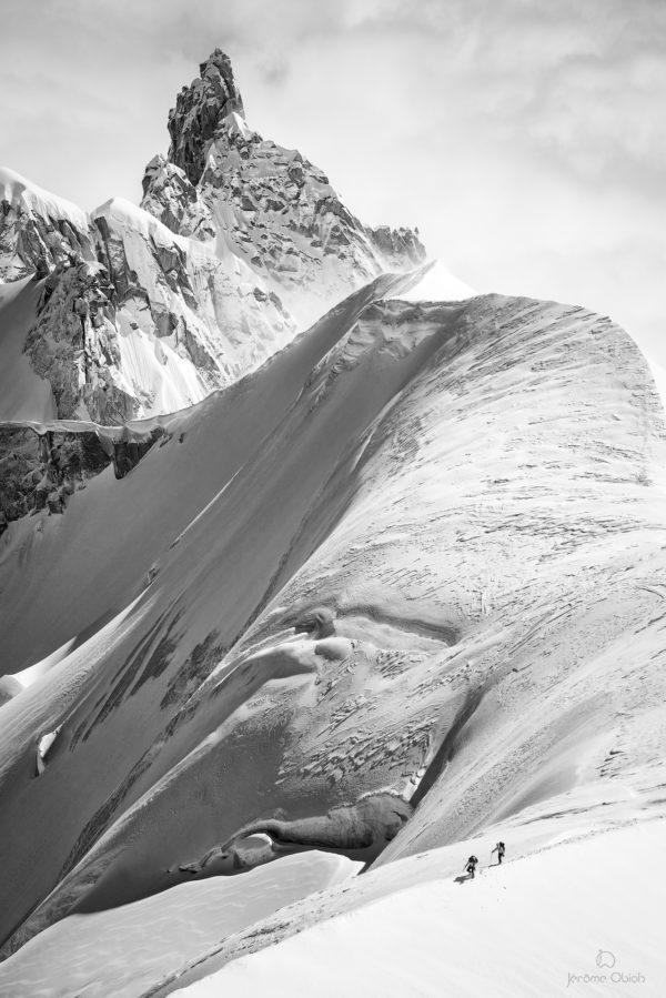 Cordée d'alpinistes sur une arête de neige devant la Dent du Requin.