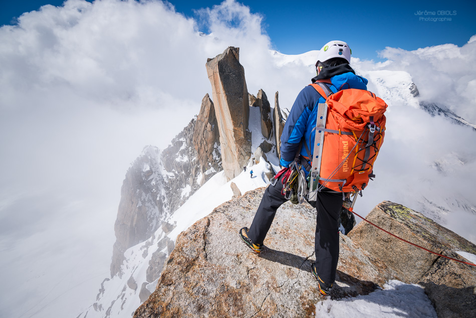 Alpiniste avec un sac a dos Patagonia sur l'Arete des Cosmiques