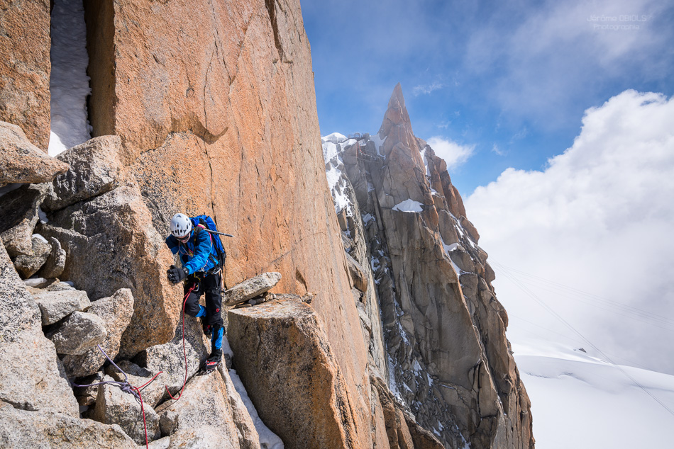 Alpiniste contournant un bloc devant la face Sud de l'Aiguille du Midi