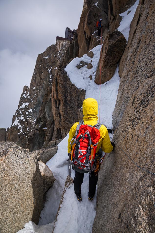Alpiniste en jaune sur une vire de neige