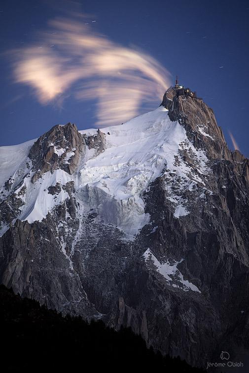 Nuages nocturnes semblant s'échapper du sommet de l'Aiguille du midi la nuit. Massif du Mont-Blanc.