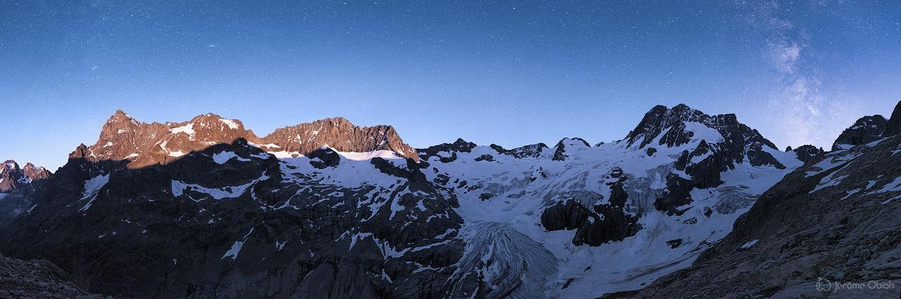 Panorama sur le cirque et le glacier de la Pilatte de nuit. La lune se couche et éclaire l'Ailefroide tandis que la voie lactee surplombe les Bans. Parc National des Ecrins.