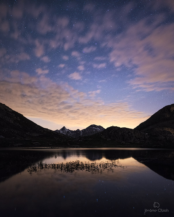 La pollution lumineuse issue de Grenoble et de la vallée du Grésivaudan illumine le ciel et se reflète dans un lac de montagne.
