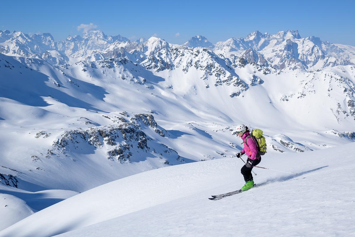 Skieuse alpiniste descendant face au massif des Ecrins. Tour du Mont-Thabor. Massif des Cerces