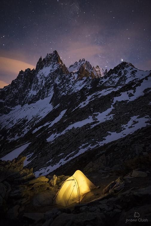 Bivouac en tente sous les etoiles au Signal Forbes sous les Aiguilles de Chamonix la nuit. Massif du Mont-Blanc.