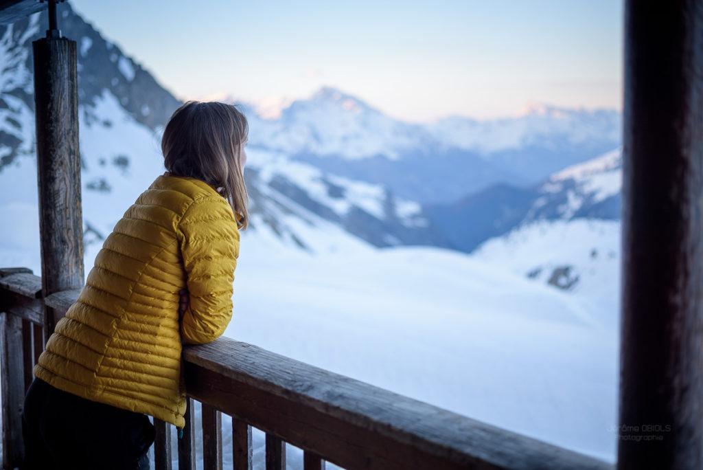 Femme accoudée sur la terrasse du refuge du Mont-Thabor contemplant la montagne. Massif des Cerces.